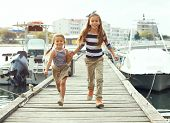 picture of marines  - Two fashion kid girls wearing navy clothes in marine style walking in the sea port - JPG