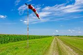 stock photo of wind-vane  - The control of a wind direction windsock inflated by the wind on the cloudy sky