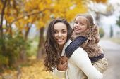 stock photo of fall day  - Young mother with her little daughter walking in fall park on yellow fallen leaves one autumn day - JPG