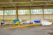 stock photo of glider  - Covered gliders are resting in hangar due to the off duty - JPG