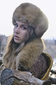 stock photo of early 20s  - portrait photo of blond hair wind girl looking to camera wearing fur hat in early spring - JPG