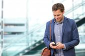 image of sms  - Young urban professional man using smart phone in office building indoors - JPG