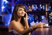 stock photo of handphone  - Young attractive lady at bar talking on phone - JPG