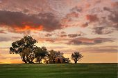 picture of farm landscape  - Australian outback sunset. Old farm house crumbling walls and verandah with two water tanks sits abandoned on a hill at sunset. The last sun rays stretching across the landscape painting the grass in dappled light