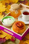 pic of bap  - cup of tea honey yogurt and pumpkin muffin on a tray on background of autumn leaves - JPG
