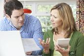 image of conflict couple  - Worried Couple Discussing Domestic Finances At Home - JPG