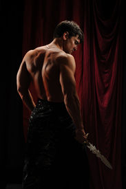 stock photo of paranormal  - the handsome rebel stands holding a sword - JPG