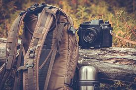 stock photo of thermos  - Lifestyle hiking camping equipment retro photo camera backpack and thermos outdoor forest nature on background - JPG