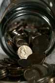 pic of spare  - Highlighted nickel resting in the middle of spare change coming out of a glass jar - JPG