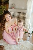 picture of pink eyes  - Young beautiful woman and mother, brunette with long curly hair and gray eyes, wearing a pink dress is holding her little daughter, with short hair and big eyes, wearing a pink dress, playing together at home in the room.
