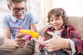 stock photo of grandpa  - Toddler boy and his grandpa are playing with a plane toy - JPG