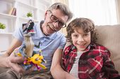 stock photo of grandpa  - A preschooler and his grandpa happily are playing with toy dinosaurs - JPG