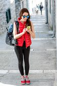 foto of sportswear  - Young woman in red sportswear looking where to go with smart phone traveling in the old city center - JPG