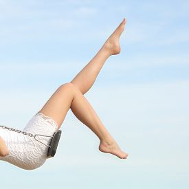 stock photo of swing  - Perfect woman waxing hair removal legs swinging with the blue sky in the background - JPG
