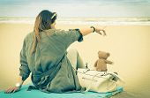 picture of nostalgic  - Young single woman sitting at the beach with her teddy bear looking at the sea  - JPG