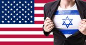 stock photo of israeli flag  - Businessman stretching suit with Israel flag on american flag background - JPG