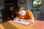 stock photo of homework  - boy doing homework for school at home - JPG