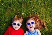 stock photo of environment-friendly  - Carefree friends in sunglasses lying on green grass - JPG
