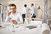 stock photo of sms  - Serious businessman writing or reading sms in working environment - JPG
