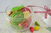 picture of jar jelly  - Colorful jelly rolls in a decorated glass jar on a decoupage decorated table - JPG