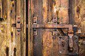 picture of wooden door  - iron rusty deadbolt on old wooden door - JPG