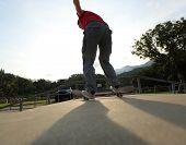 pic of skateboard  - closeup of skateboarder legs skateboarding at skatepark ramp - JPG
