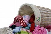 stock photo of dirty-laundry  - a pile of diry clothes overflows from a young girls laundry basket - JPG