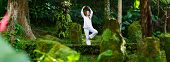 foto of tranquil  - Panorama pf young woman doing yoga outdoors in tranquil environment - JPG
