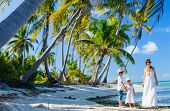 stock photo of deserted island  - Beautiful family of mother and two kids on a deserted island - JPG