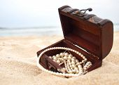 stock photo of treasure  - Treasure chest in the sand by the sea - JPG