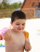 picture of little boys only  - little boy eating sweet candy class and shows his hand - JPG