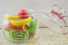 image of decoupage  - Colorful jelly rolls in a decorated glass jar on a decoupage decorated table - JPG