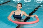 Happy smiling woman doing exercise with aqua tube in a swimming pool. Young sportive woman exercisin poster