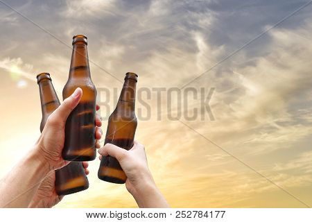 Hands Holding Three Beer Bottles