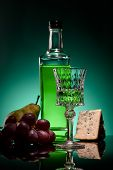 Close-up Shot Of Absinthe With Ripe Fruits And Cheese On Mirror Surface On Dark Blue Background poster