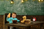 Pupil Eat Food At Wooden Table. Little Pupil Enjoy Lunch Break In Classroom. School Menu For Pupil.  poster