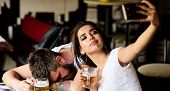 Take Selfie To Remember Great Event. Woman Making Fun Of Drunk Friend. Man Drunk Fall Asleep Table A poster
