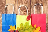 Autumn Shopping. Fallen Leaves On Paper Bags. Flat Lay. Autumn Sales. Shopping Bags On Wooden Backgr poster