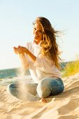 Joy And Carefree. Gorgeous Long Haired Woman Having Fun With Sand On Beach. Young Joyful Attractive  poster