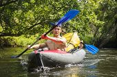 Kayaking On River. Athletic Guys In Canoe Rowing With Oars. Active Recreation In Nature. Water Adven poster