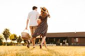 Back view image of young couple with basket of drinks and food going to have picnic outdoors. poster