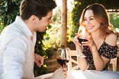 Picture of young loving couple sitting in cafe by dating outdors in park holding glasses of wine dri poster