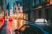 Taxi Car Wait Clients In Old European Streets  In Rainy Evening. poster
