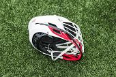 A Red And White High School Lacross Helmet Left On A Green Turf Field. poster