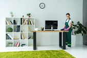 Young Cleaning Company Worker In Rubber Gloves And Uniform Cleaning Desk In Modern Office poster