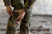 Soldier Puts Knee Pads On
