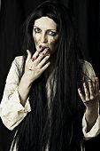 stock photo of gory  - Portrait of a gory bloody and scary zombie woman on black background - JPG