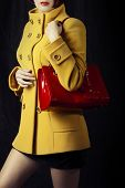 picture of outerwear  - Fashion portrait of beautiful woman in yellow spring or autumn coat with red bag - JPG