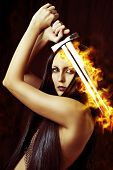 foto of sorcerer  - Young sexy woman warrior holding fire sword in hands with long healthy black hair - JPG
