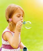 Closeup portrait of cute baby girl blowing soap bubbles in spring park, having fun outdoors, happy c